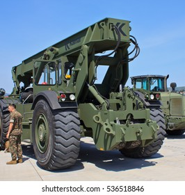 IWAKUNI, JAPAN - MAY 5, 2016: A marine stands in front of a green army construction vehicle with giant rubber tires under a blue sky at the U.S. Marine Corps Air Station in Iwakuni.