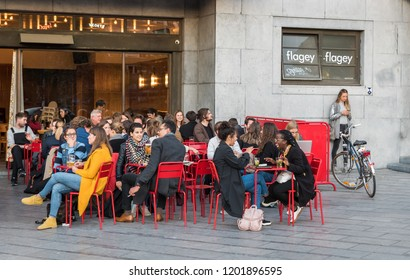 Ixelles, Brussels / Belgium - 10 09 2018: Young people having a drink on a sunny terrace on a late summer evening at the Belga Queen, Flagey