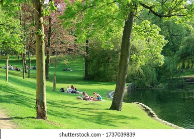 Ixelles, Bruxelles / Belgium - 10 May 2019: People chilling relaxing on green lawn meadow étangs d'ixelles flagey lakes trees shadow picnic reading tanning sunday afternoon sunny