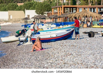 Ixia, Rhodes, Greece - June 05, 2018. Afternoon view on a beach in Ixia, small fishing boat and people next to the sea