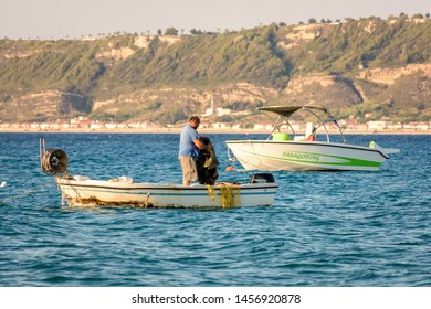 Ixia, Rhodes, Greece - June 05, 2018. A fisherman working with net on small fishing boat on the Aegean sea in Ixia