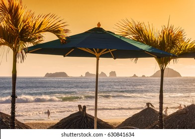 Ixtapa, Mexico beach scene with beach umbrella, palm trees, and ocean and rocks background