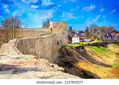 Izborsk fortress and village, Pskov region, Russia. Beautiful scenic view, ruined stone wall and tower of ancient citadel (Kremlin) and small christian chapel at the background of cloudy blue sky