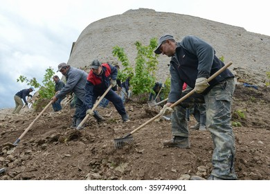 Izborsk, Pskov region, Russia - May 31, 2012: A group of workers engaged in the reconstruction and restoration of the tower and the protective walls of the fortress in the summer sunny day.