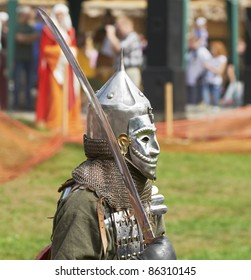 """IZBORSK, RUSSIA - AUGUST 6: Unidentified man in a knightly armor take part in festival """"Iron hailstones"""" on August, 6 2011 in Izborsk, the Pskov area, Russia."""
