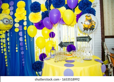 Izmail, Ukraine - 2016. Birthday party with minions design. Cartoon character balloons. Thematic event. Candy bar with fruit plate and glasses. Inscription reads Vanya is 1 year old.