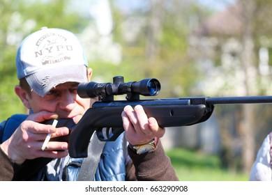IZMAIL, UKRAINE - APRIL 22, 2017: Guy shoots a gun. Man aims an air rifle