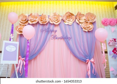 Izmail, Ukraine - March 2016. Beautiful pink photo zone for three years old girl with paper flowers, balloons, curtains. Inscription in Russian reads Amelia is 3 years oldHappy Birthday concept.