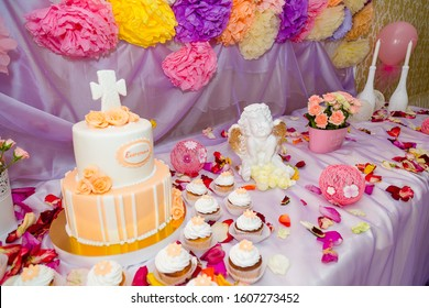 Izmail, Ukraine - summer 2016. Editorial. Baptism candy bar, angel statue, cupcakes, unfocused cake. Mastic cross on cake for christening child party. White candles and flower petals on the table.
