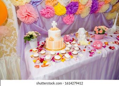 Izmail, Ukraine - summer 2016. Editorial. Baptism candy bar, angel statue, cupcakes. Mastic cross on cake for christening child party. White candles and flower petals on the table.