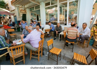 IZMIR PROVINCE, TURKEY - JUL 28: Senior men sitting around tables and talking in rustic cafe of old village on July 28, 2015. Population of Izmir province is 3.950.000 people