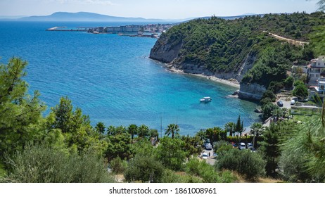 Izmir, Turkey - 15.09.2018: Paradise view from mountain to secret bay with nice beach and blue water with boat. Mountain on horizon.