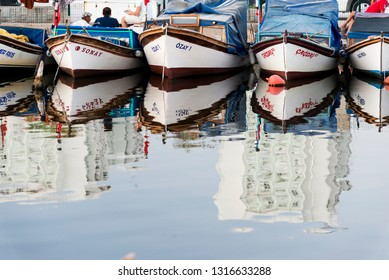 Izmir, Turkey - August  12, 2018: Various fisher boats parked in the shelter with reflection. Bostanli fishing shelter Izmir Turkey.