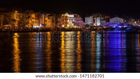 Izmir, Turkey - August 2 2019 : The night view of Eski Foca (in EN: old Phokaia) with lights reflected over the sea. Seaside is crowded and the people are hanging around.