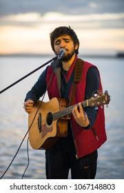 Izmir, Turkey - Circa December 2017 - A shot of an unidentified street performer singing and playing guitar near Konak Pier in Izmir, Turkey