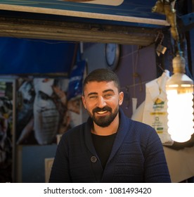 Izmir, Turkey - Circa December 2017 - A close up portrait shot of an unidentified fish seller in Izmir wet market smiling happily