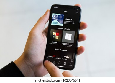 IZMIR ,TURKEY - JANUARY 14, 2018: Smartphone Apple Iphone 10 X Space Silver Grey Color. Young Man with hand Open apps Spotify application at screen on white background.