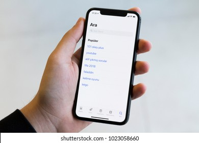 IZMIR ,TURKEY - JANUARY 14, 2018: Smartphone Apple Iphone 10 X Space Silver Grey Color. Young Man with hand Open App Store application at screen on white background.