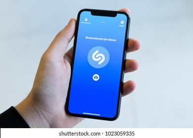 IZMIR ,TURKEY - JANUARY 14, 2018: Smartphone Apple Iphone 10 X Space Silver Grey Color. Young Man with hand Open apps Shazam application at screen on white background.