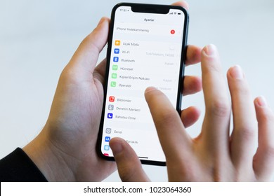 IZMIR ,TURKEY - JANUARY 14, 2018: Smartphone Apple Iphone 10 X Space Silver Grey Color. Young Man with hand Open Setting application at screen on white background.