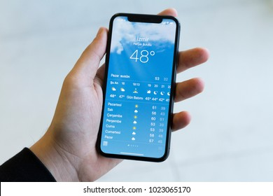 IZMIR ,TURKEY - JANUARY 14, 2018: Smartphone Apple Iphone 10 X Space Silver Grey Color. Young Man with hand Open apps Weather application at screen on white background.