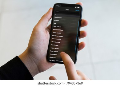 IZMIR ,TURKEY - JANUARY 14, 2018: Smartphone Apple Iphone 10 X Space Silver Grey Color. Young Man with hand Open apps social networking service CONTACTS application at screen on white background.