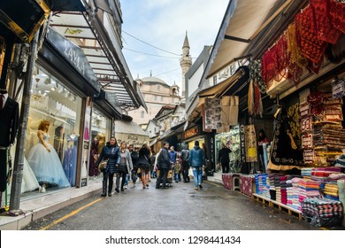Izmir, Turkey - January 26, 2019. Street view in Kemeralti market in Izmir, with shops and people, toward Sadirvan mosque.