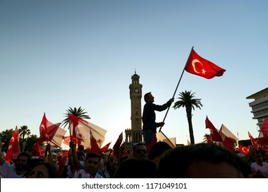 Izmir, Turkey - July 15, 2018: July 15 Day of Democracy in Turkey Izmir. People holding Turkish flags at Konak square in Izmir and in front of the historical clock tower.