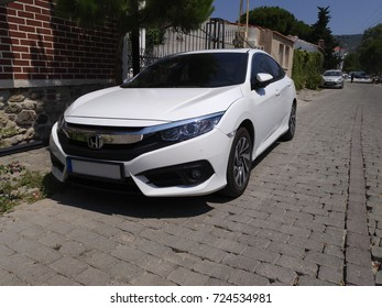 Izmir, Turkey - July 19, 2017: New white Honda Civic at The Izmir Streets in a sunny day in a district. There is nobody in the car.