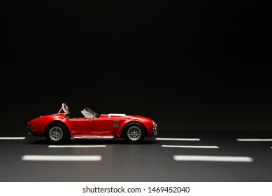 Izmir, Turkey - July 28, 2019: Red Ford Shelby 427 Cobra Toy car on a black background and road lanes.