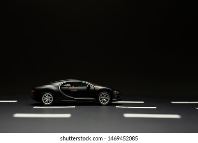 Izmir, Turkey - July 28, 2019: Side view of a Black Bugatti Veyron Toy car on a black background and road lanes.