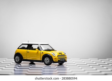 Izmir, Turkey - June 01, 2015.  Mini Cooper S Toy car on white background and checked floor.