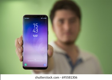 Izmir, Turkey - JUNE 26, 2017: Man shows new Smartphone Samsung Galaxy S8 Plus Orchid Grey Color screen in his hand. Samsung Group is a South Korean multinational conglomerate headquartered in Seoul.