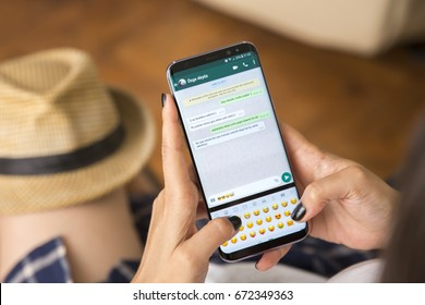 IZMIR ,TURKEY - JUNE 27, 2017: Smartphone Samsung Galaxy S8 Plus Orchid Grey Color. Young Women with black nail polish Open apps WHATSAPP application on the screen on rustic brown wood background.