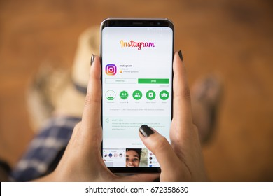IZMIR ,TURKEY - JUNE 27, 2017: Smartphone Samsung Galaxy S8 Plus Orchid Grey Color. Young Women with black nail polish Open apps INSTAGRAM application on the screen on rustic brown wood background.