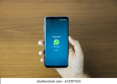 IZMIR ,TURKEY - JUNE 27, 2017: Smartphone Samsung Galaxy S8 Plus Orchid Grey Color. Young Women with Open apps WHATSAPP application on the screen on rustic brown wood background.