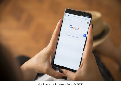 IZMIR ,TURKEY - JUNE 27, 2017: Smartphone Samsung Galaxy S8 Plus Orchid Grey Color. Young Women with black nail polish Open apps GOOGLE application on the screen on rustic brown wood background.