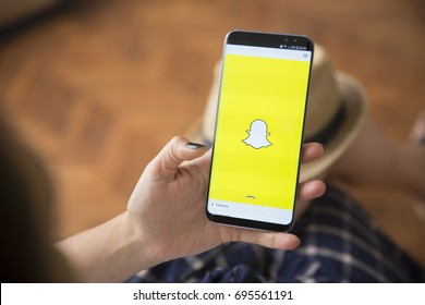 IZMIR ,TURKEY - JUNE 27, 2017: Smartphone Samsung Galaxy S8 Plus Orchid Grey Color. Young Women with black nail polish Open apps SNAPCHAT application on the screen on rustic brown wood background.