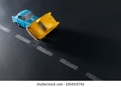 Izmir, Turkey - March 24, 2018: Traffic accident by two toy cars blue and yellow on a black background with road lanes.