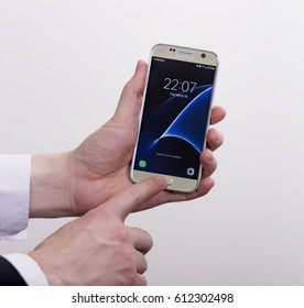 Izmir, Turkey - March28, 2017: Young man holding brand new android smart phone Samsung galaxy S7 on white background.