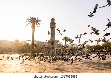 Izmir, Turkey - November 10, 2018: Clock tower and some people at Konak Square Izmir Turkey and in the morning with flying pigeons.