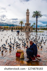 Izmir, Turkey - November 26, 2015 : Konak square and birdseed seller around view on  in Izmir. The Izmir Clock Tower is the most recognized landmark of the city.
