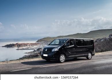 Izola, Slovenia-03.03.2019: Black Van for transport or delivery with mediterranean landscape