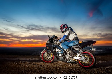 IZYUM, UKRAINE - September 25, 2015: Motorcyclist on sport bike stands on the edge of the mountains in the background of a bright sunset. Man look to the left side.