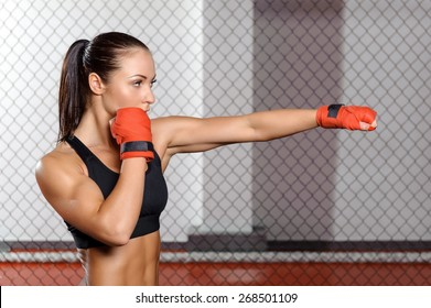Jab. Young strong and fit woman training her jab in a fighting cage