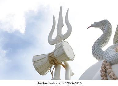 JABALPUR, INDIA - AUGUST 07: Closeup of drum, trident & snake of the 76 feet tall Lord Shiva statue on August 07, 2012 at Kachnar City, Jabalpur, India. This is one of the tallest statues in India