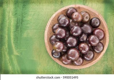Jaboticaba (brazilian berry) on wooden table (Plinia cauliflora)
