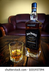 Jack Daniel's Frank Sinatra edition whiskey bottle and glass on wooden pallet table in man's cave leather couch background