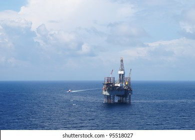 Jack up drilling rig and crew boat on sunny day