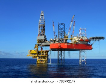 Jack up drilling rig on oil well platform with blue sky background
